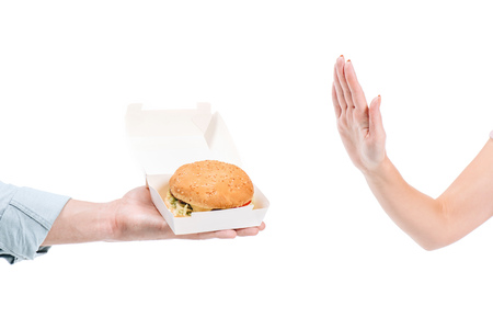 cropped image of woman rejecting unhealthy burger isolated on white 版權商用圖片