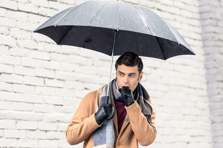 stylish man in coat and scarf with umbrella standing in front of brick wall on street Stock Photo - 112222640