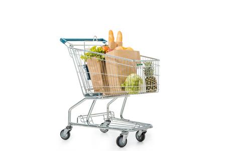 Papiertüten voller Produkte im Einkaufswagen isoliert auf weiss
