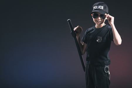 portrait of boy in policeman uniform and sunglasses on dark background
