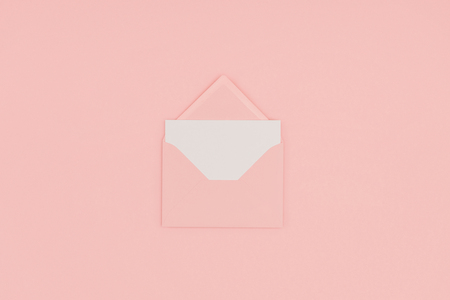 top view of open pink envelope with blank white card isolated on pink Stok Fotoğraf