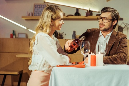 handsome man in jacket pouring wine into glass to beautiful girlfriend at table in restaurant Stok Fotoğraf