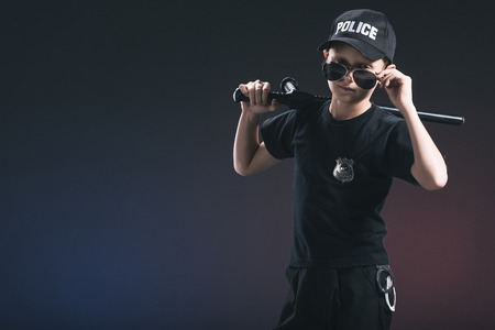portrait of boy in policeman uniform and sunglasses with truncheon on dark background 스톡 콘텐츠
