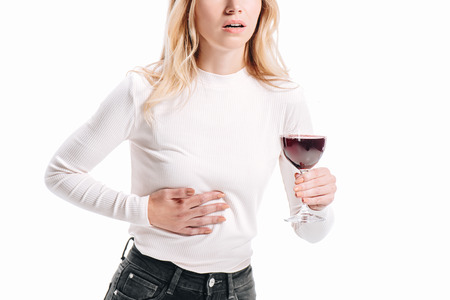 immagine ritagliata di una donna che mostra dolore al fegato e tiene in mano un bicchiere di vino rosso isolato su bianco Archivio Fotografico