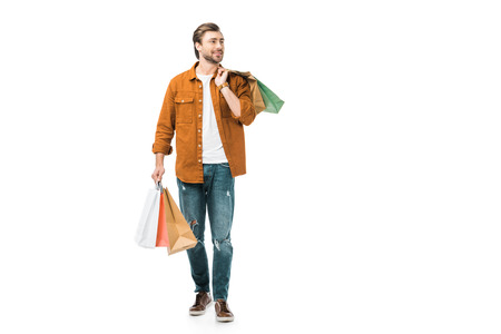happy man walking with colorful shopping bags isolated on white Reklamní fotografie