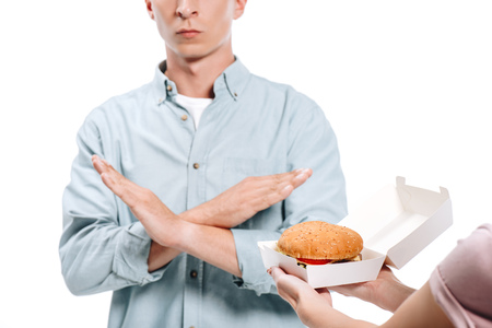 cropped image of man showing no sign to woman proposing burger isolated on white Imagens