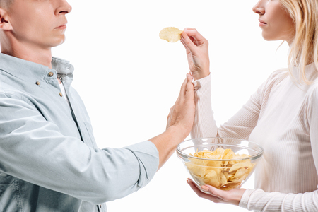 cropped image of man rejecting unhealthy potato chips from woman isolated on white Stock Photo