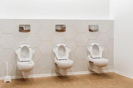 clean white toilet bowls in toilet in modern kindergarten Stock Photo