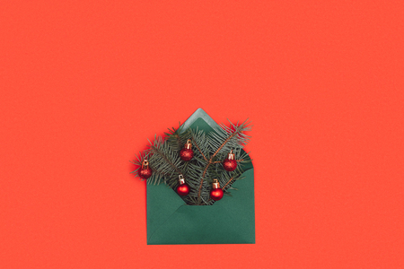 close-up view of green envelope with fir twigs and shiny christmas baubles isolated on red Stock Photo