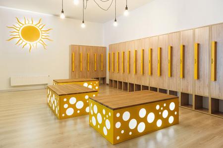wooden lockers in modern illuminated kindergarten cloakroom Stock Photo