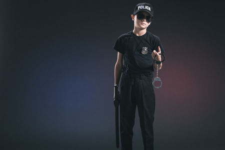 boy in policeman uniform and sunglasses with handcuffs on dark background