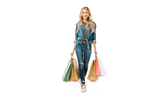 attractive stylish young woman walking with colorful shopping bags isolated on white