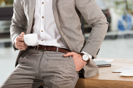 cropped shot of businessman with cup of coffee leaning back at workplace Stock Photo