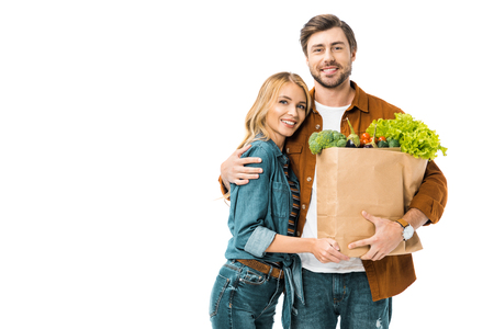 young man holding paper bags with products and embracing girlfriend isolated on white Фото со стока