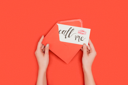 cropped shot of person holding red envelope and card with kiss mark and call me inscription isolated on red