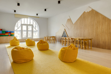 yellow bean bag chairs and wooden tables in kindergarten playing room 스톡 콘텐츠