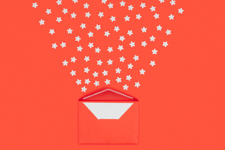 close-up view of red envelope with blank card and small white stars isolated on red Stock Photo