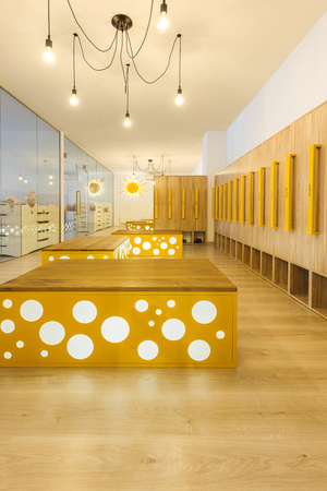 wooden lockers, benches and mirror in illuminated kindergarten cloakroom