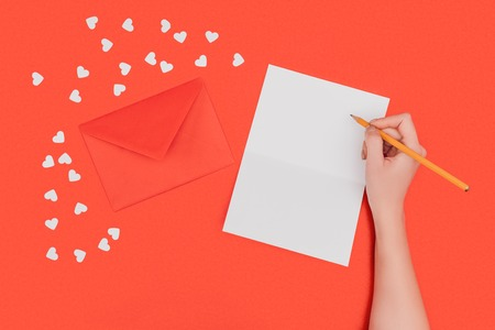 cropped shot of person writing in white card, red envelope and small hearts isolated on red Stock Photo
