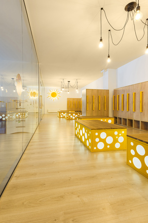 wooden lockers, benches and mirror in modern illuminated kindergarten cloakroom