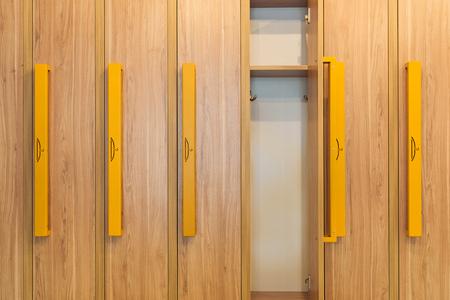 wooden lockers with yellow handles in kindergarten cloakroom Zdjęcie Seryjne