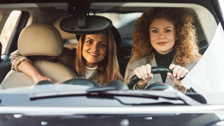 Curly ginger woman driving car while her smiling female friend sitting on backseat
