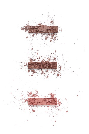 Flat lay with arranged eye-shadows of brown shades isolated on white