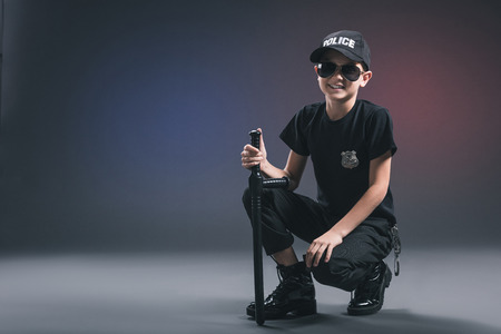Smiling boy in policeman uniform and sunglasses on dark background
