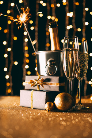 champagne in bucket, presents and christmas sparkle on garland light background