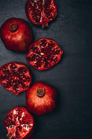 top view of ripe pomegranates arrangement on black surface