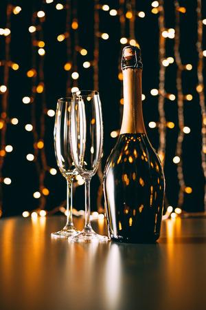 Botella de champán y copas sobre fondo claro Garland, concepto de Navidad