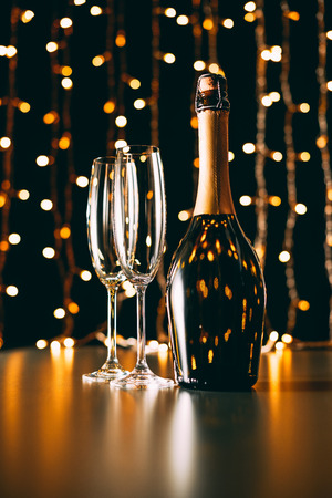champagne bottle and glasses on garland light background, christmas concept