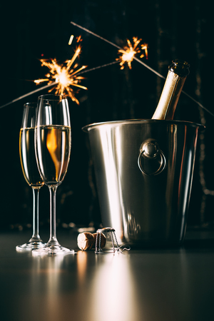 champagne bottle in bucket and christmas sparkles on dark background Stock Photo