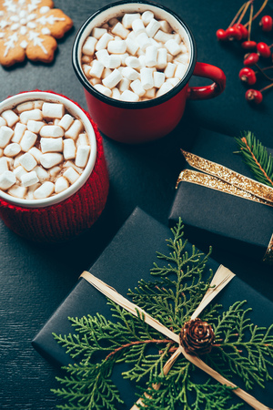 Top view of wrapped Christmas presents and cups of hot chocolate with marshmallows on black tabletop