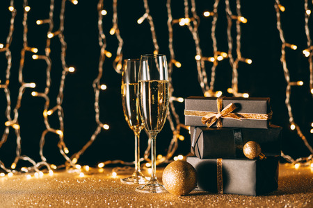 Christmas presents and glasses of champagne on garland light background