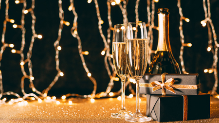two glasses of champagne, presents and bottle on garland light background, christmas concept Stock Photo