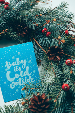 Top view of pine tree branches and winter postcard with baby its cold outside lettering on white tabletop Stock Photo