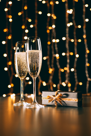 Glasses of champagne and present on garland light background, Christmas concept