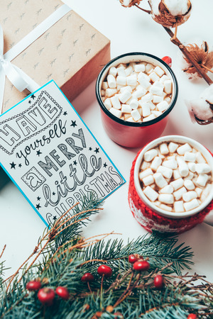 top view of postcard with have yourself marry little christmas lettering, present and cups of cocoa drinks with marshmallows on white tabletop