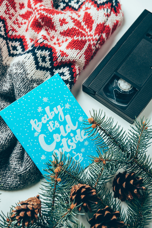 top view of video cassette, sweater and postcard with baby its clod outside lettering on white surface Stock Photo - 112156509