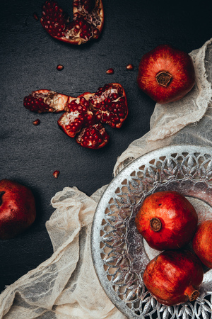 Food composition with ripe and fresh pomegranates, metal bowl and gauze on black tabletop