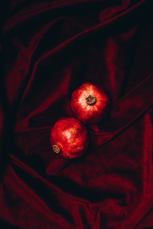 top view of ripe pomegranates on red velvet fabric backdrop
