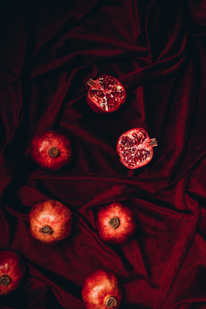top view of arranged pomegranates on red velvet fabric background Stock Photo