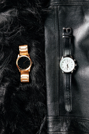 Top view of luxury masculine and feminine wrist watches on black leather and woolen background Фото со стока
