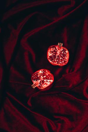 top view of ripe garnet halves on red velvet fabric background