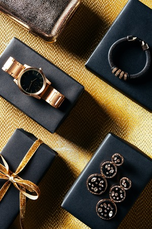 flat lay with wrapped gift, feminine jewelry and purse on golden backdrop Stockfoto