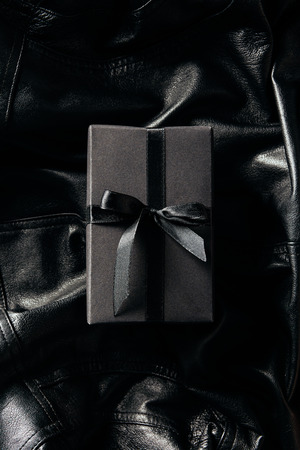 top view of black wrapped gift on black leather jacket background Standard-Bild
