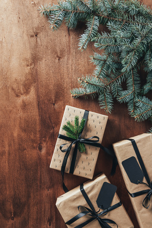 flat lay with christmas presents, fir branches and tags on wooden background with copy space