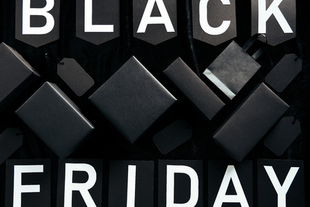 top view of black friday lettering, blank price tags, shopping bag and boxes on black background