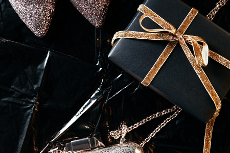 top view of arrangement with wrapped present, feminine shoes and purse on black wrapping paper backdrop